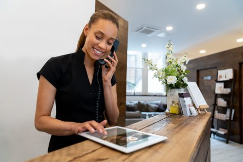IEN Hospitality Sector Receptionist talking on the phone & handling an online booking